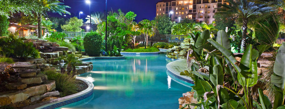 View of the Lazy River in the evening with the lights glimmering on the water at the Holiday Inn Orange Lake Resort in Kissimmee Fl