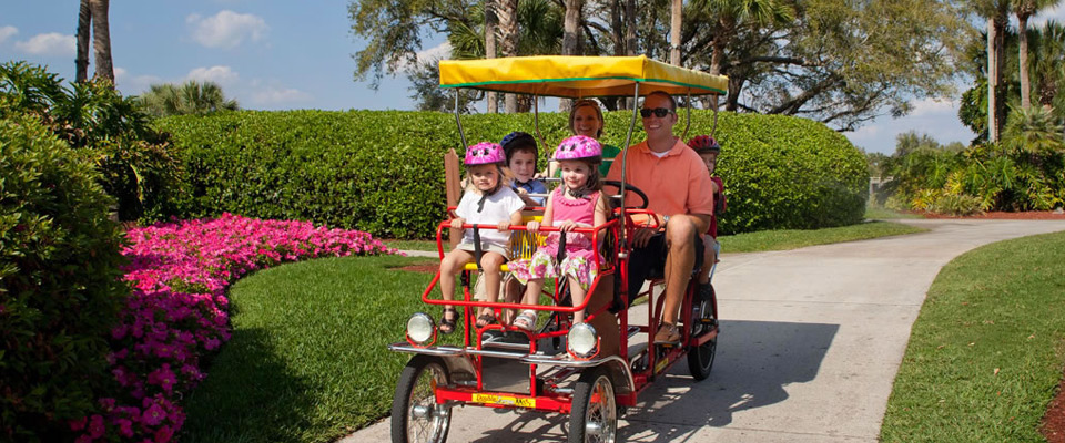 A family taking a ride through the Hyatt Regency Grand Cypress Resort on a covered Surrey Bike