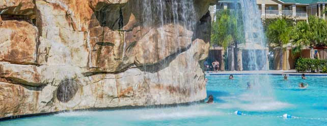 Water Slide built into the 2-story rock waterfall feature at the Dunes Lagoon heated pool at the Mystic Dunes Resort in Orlando