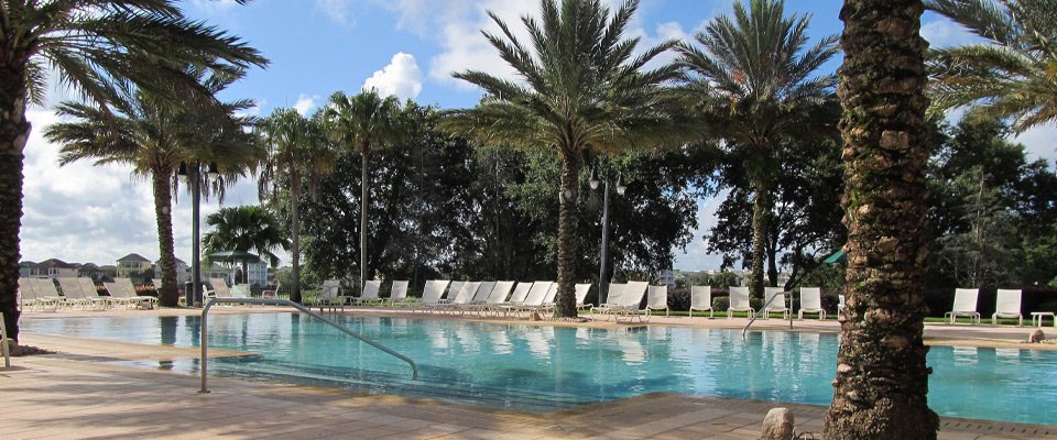 View of the Seven Eagles Pool with beautiful Palms and Lounge Chairs at Reunion Resort