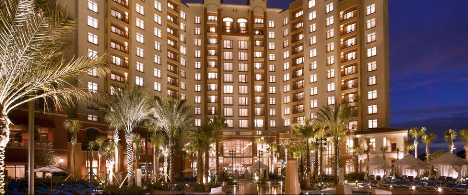 Evening View of the Wynham Grand Orlando at Bonnet Creek lit up from the Pool with Cabanas in the background 960