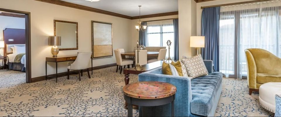 A very large living space with plenty of seating looking in to the private bedroom of the Junior Presidential Suite at the Wyndham Grand Orlando